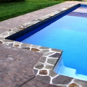 Natural blue stone coping with stamped concrete decking. Liner Pattern: Indigo Marble/Blue Granite