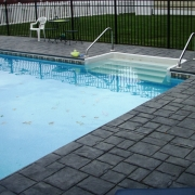 Stamped concrete decking with cantilevered concrete coping and non-cantilevered step. Liner Pattern: Canyon/ Crystal