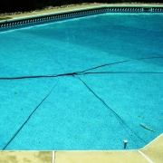 "BEFORE - Pool with a ""star wrinkle"". This is usually caused by the vinyl liner floating from heavy rains."