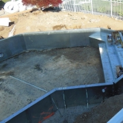 In Progress - Changed the configuration of the pool and added an 18 foot steel wall step and bench.