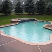 BEFORE - Freeform concrete pool with a raised spa and sheer decent wall.