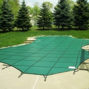 AFTER - Freeform concrete pool with a raised spa and sheer decent wall covered by a Green Mesh Safety Cover with 3' spacing.
