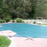 AFTER - Grecian vinyl liner pool with a raised spill-over spa and a brick paver decking covered by a Green Mesh Safety Cover with 5