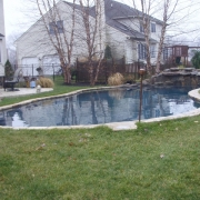 BEFORE - Freeform concrete pool with large stone waterfall with no decking.
