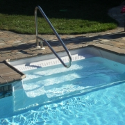 """Trojan pool with 8' polymer cantilever sit-n-step with pavers for coping, and new vinyl liner. Handrail is a """"dip to pool """"style. Liner Pattern: Canyon/Crystal"""