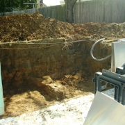 BEFORE - Trojan pool with excavation and wall prep for installation of 8' polymer step unit.
