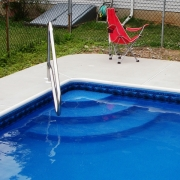 Corner wedding cake step with bullnose coping, dip to pool handrail and new concrete.