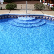 """Steel wall pool with new 180 degree """"wedding cake steps"""" (modified to fit decagon shape) and bottom color vinyl liner over step unit. Handrail is a """"dip to pool """"style."""