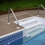 "Anthony/Sylvan pool with 8' polymer cantilever sit-n-step with new cement lock (bull nose) coping, new concrete, and new vinyl liner. 2 handrails are ""2 bend deck-to-deck"" style."