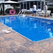 Stamped concrete with white aluminum bullnose coping.