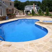 AFTER - Polymer wall pool with a liner covered step, custom sand stone coping and natural sand stone decking. A spill over spa with custom spillway and sandstone surround was also added while deleting the diving board.