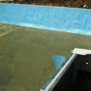 In Progress - Walls are concreted in place. The pool base is repaired with a new vermiculite / hard bottom, and foam is installed on the walls. A vinyl liner tracking is installed on top of the wall to accept the new vinyl liner.