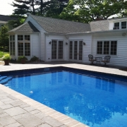After - Concrete pool with new retrofit liner, freeform step, bull nose paver coping, and paver deck.