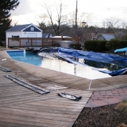 BEFORE - Wood wall pool with sagging, cracking concrete decking and loose coping.