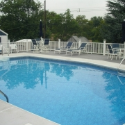 AFTER - Wood wall pool with cement lock / aluminum bull nose coping, new concrete and a Trex deck.