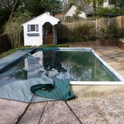 "BEFORE - Sylvan pool with 7"" aluminum coping. Note the concrete decking leaning and shifting towards the pool causing the walls to fail and start sagging and bowing in."