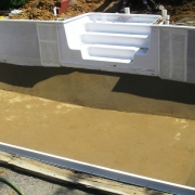 "DURING - Renovation of a wood wall ""Dream pool"" in progress. Wall foam has been installed and the sand bottom is finished."