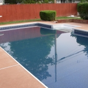 "AFTER - Wooden wall pool (""Dream Pool) with raised deep end, bullnose coping, 8'step, and new dyed concrete."