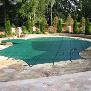 AFTER - Green Mesh Safety Cover with raised spa using custom hardware to prevent damage to hand laid sand stone deking.