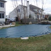 AFTER - Green Solid Safety Cover with lawn tubes and cable system.