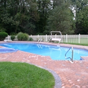 BEFORE - Grecian vinyl liner pool with a raised spill-over spa and a brick paver decking.