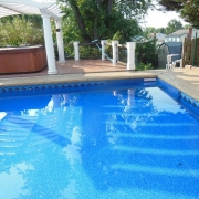 After - A rectangle pool with a Blue Granite fiberglass corner step filled with water.